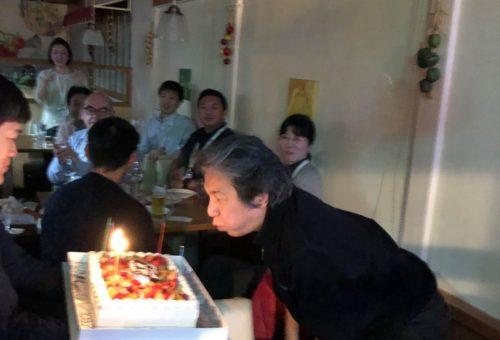 還暦祝いのケーキの蝋燭を吹き消す人事担当の矢田さん